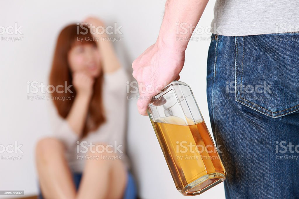 Woman cowering in corner and man with a bottle of alcohol stock photo