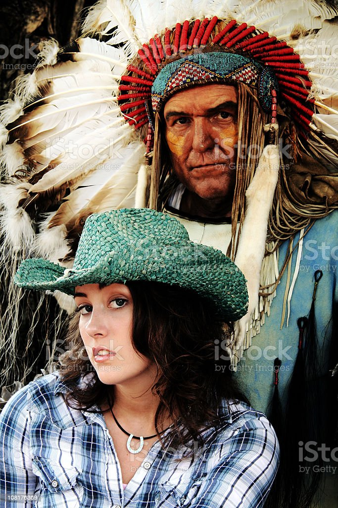 Woman Cowgirl Posing with American Indian Man Wearing Headdress stock photo