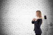 Woman crashing white brick wall with sledgehammer