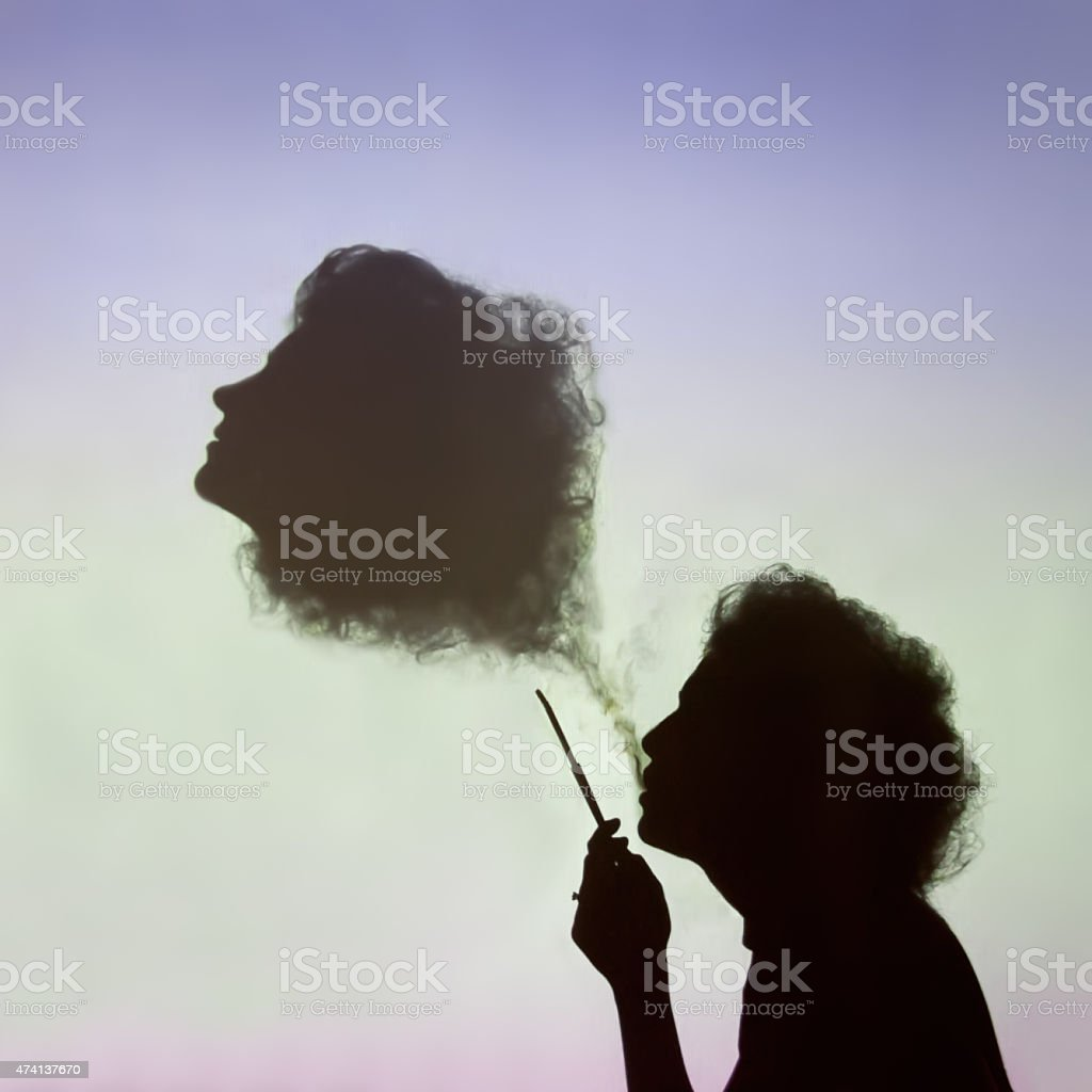Woman creates abstract figure of head from smoke. stock photo