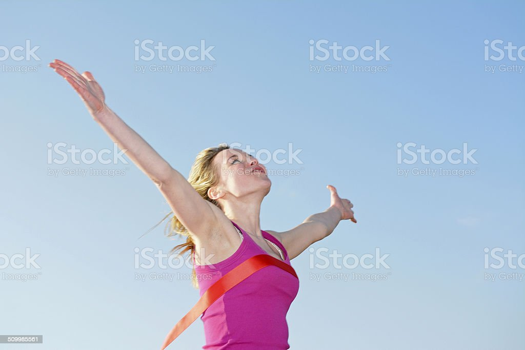 woman  crossing finishing line stock photo