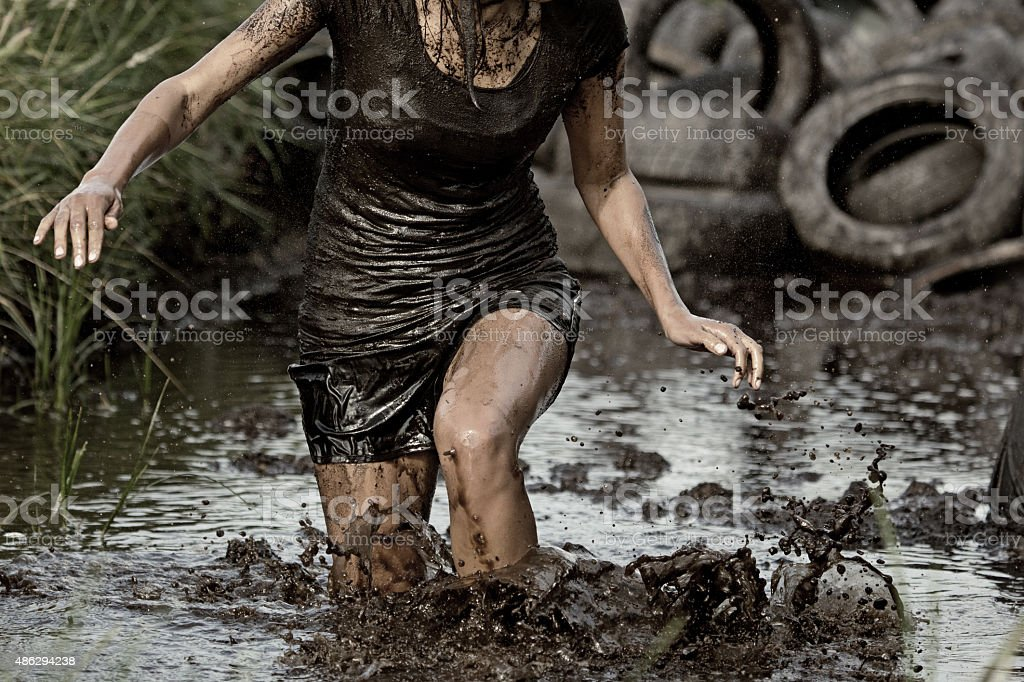 woman crossing mud obstacle stock photo