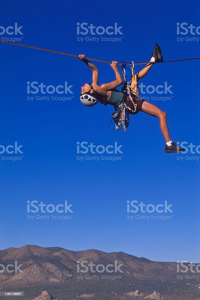 Woman crossing rope in air over mountain background stock photo
