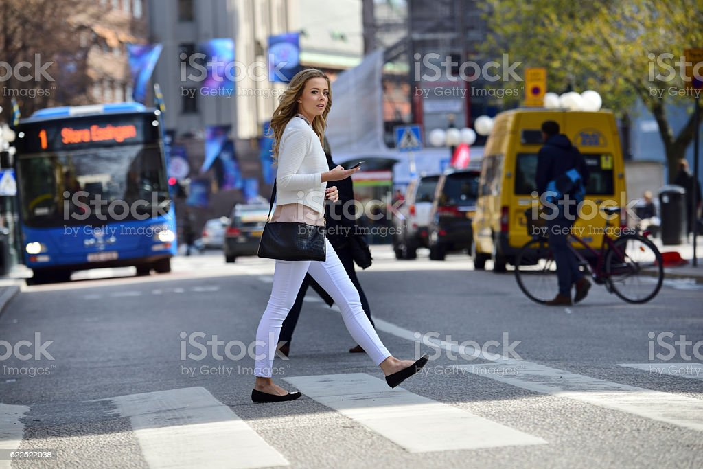 Woman crossing street, zebra crossing, bus and traffic in background stock photo