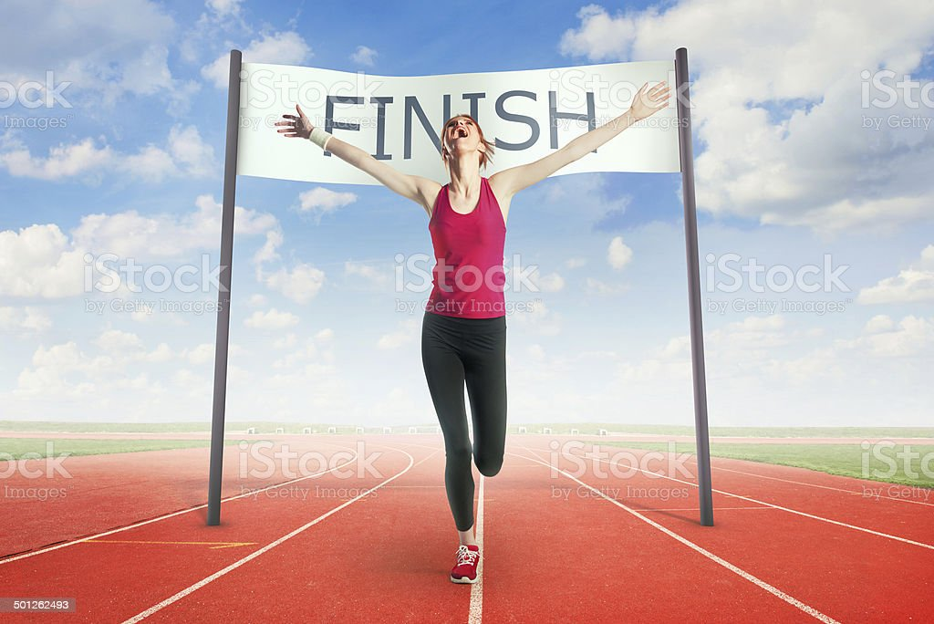 Woman crossing the finish line stock photo