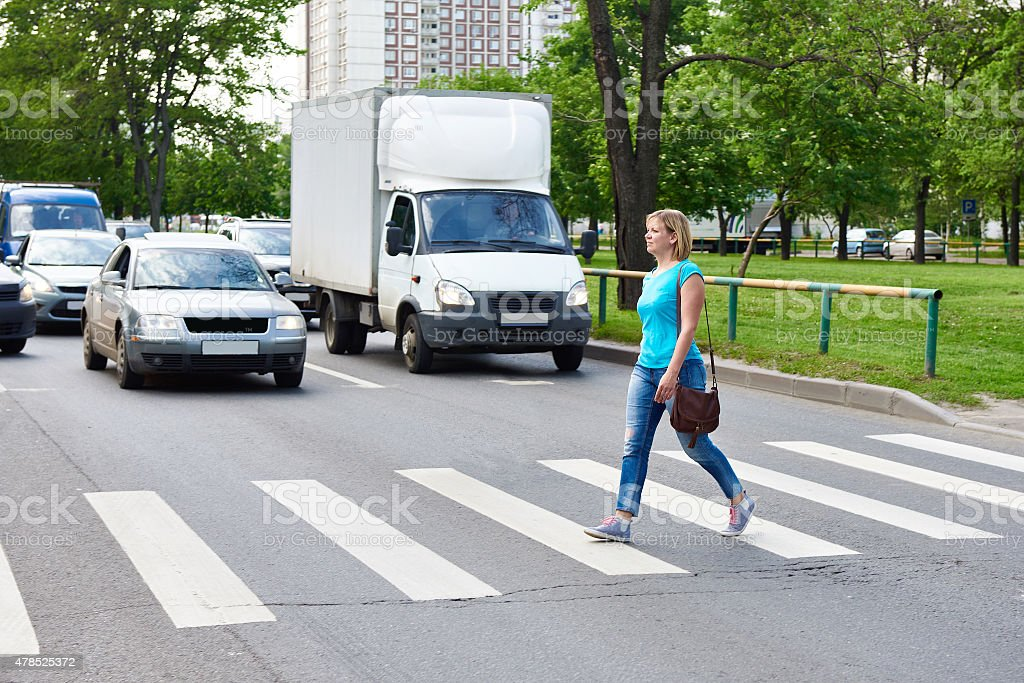 Woman crossing the street at pedestrian crossing stock photo