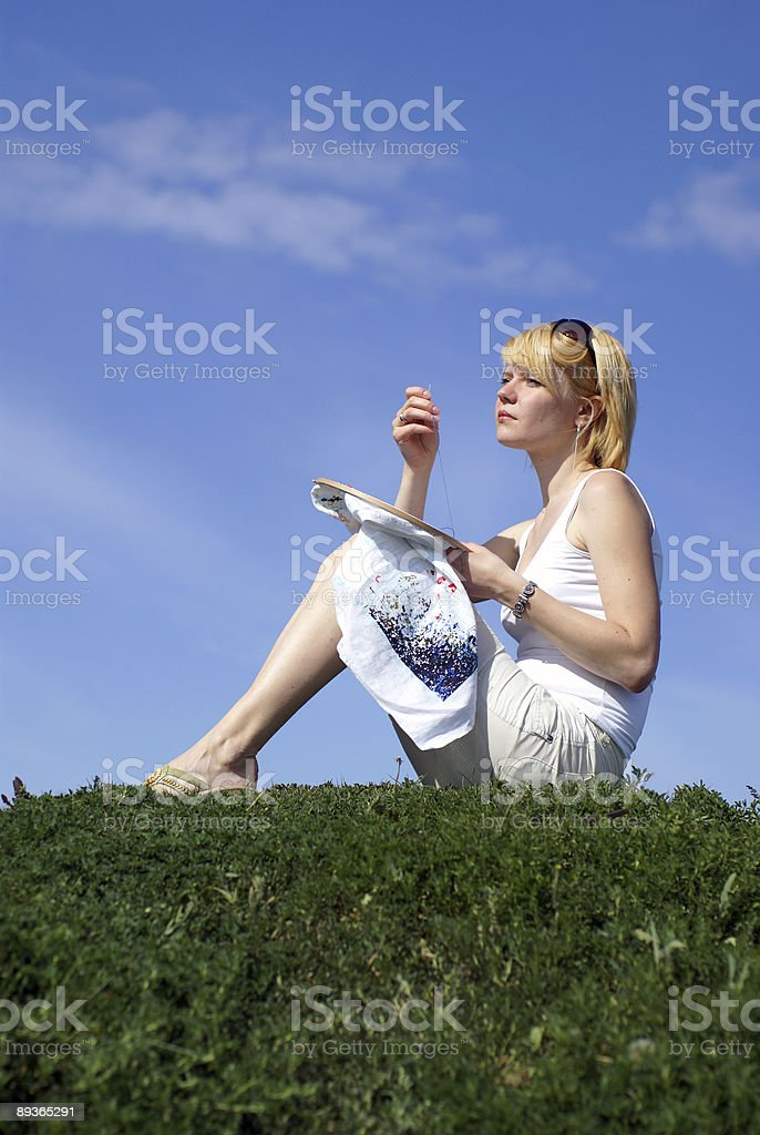woman cross-stitching in the park with blue sky on background royalty-free stock photo