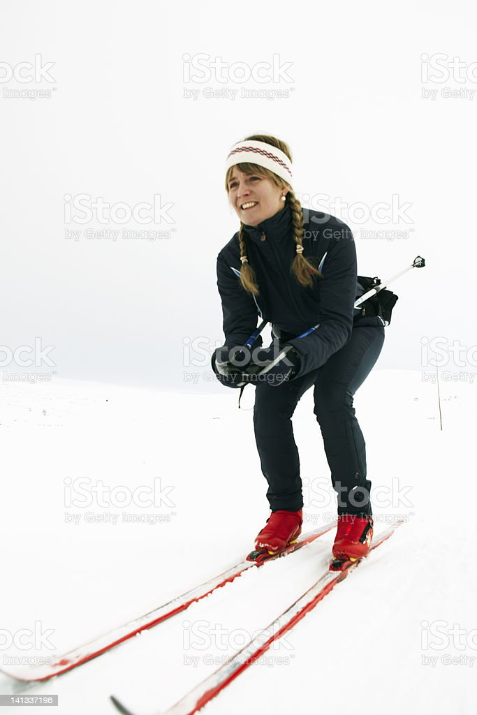 Woman crouching and cross-country skiing stock photo