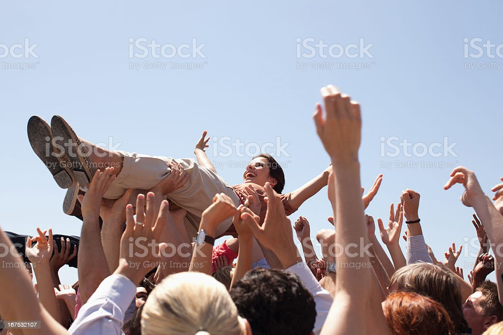 Woman crowd surfing stock photo