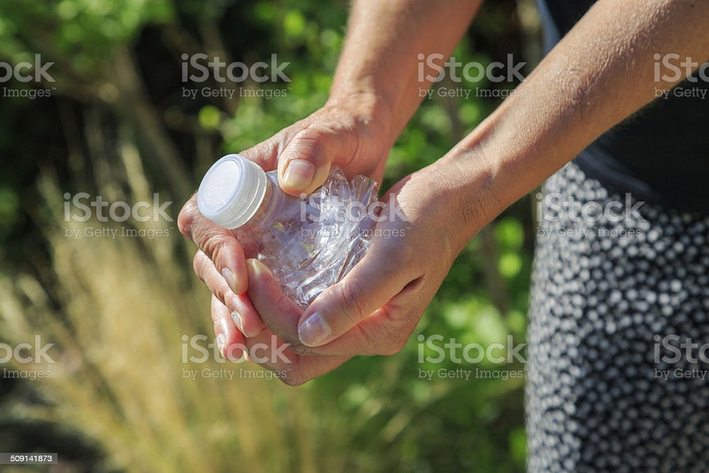 woman crushing a plastic bottle royalty-free stock photo