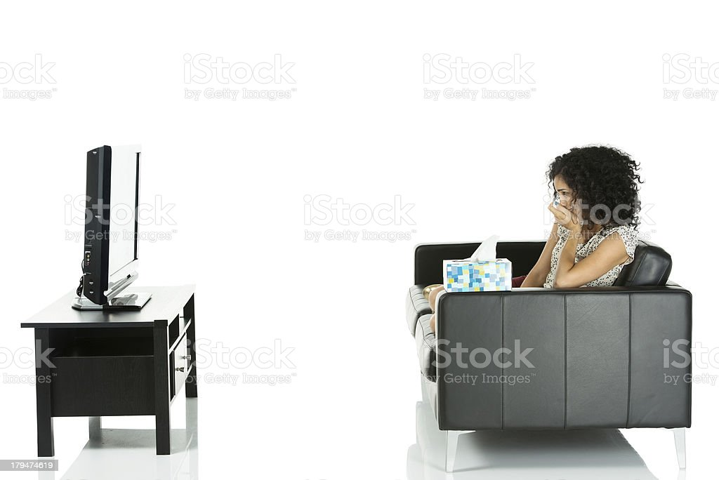 Woman crying while watching sad movie on television royalty-free stock photo