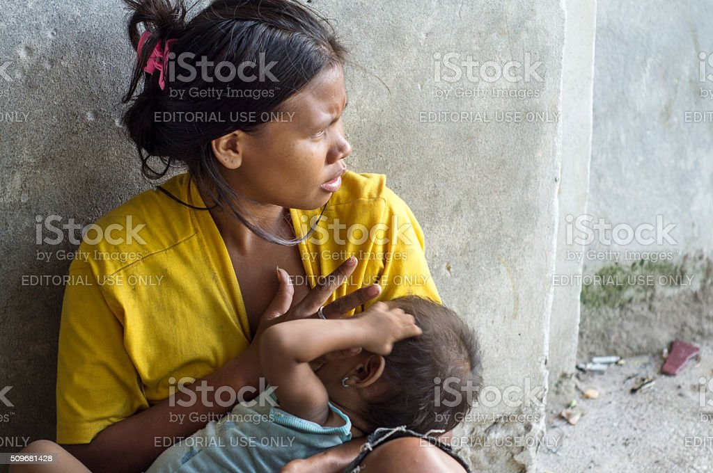 Woman cuddling a child begging at church portal stock photo