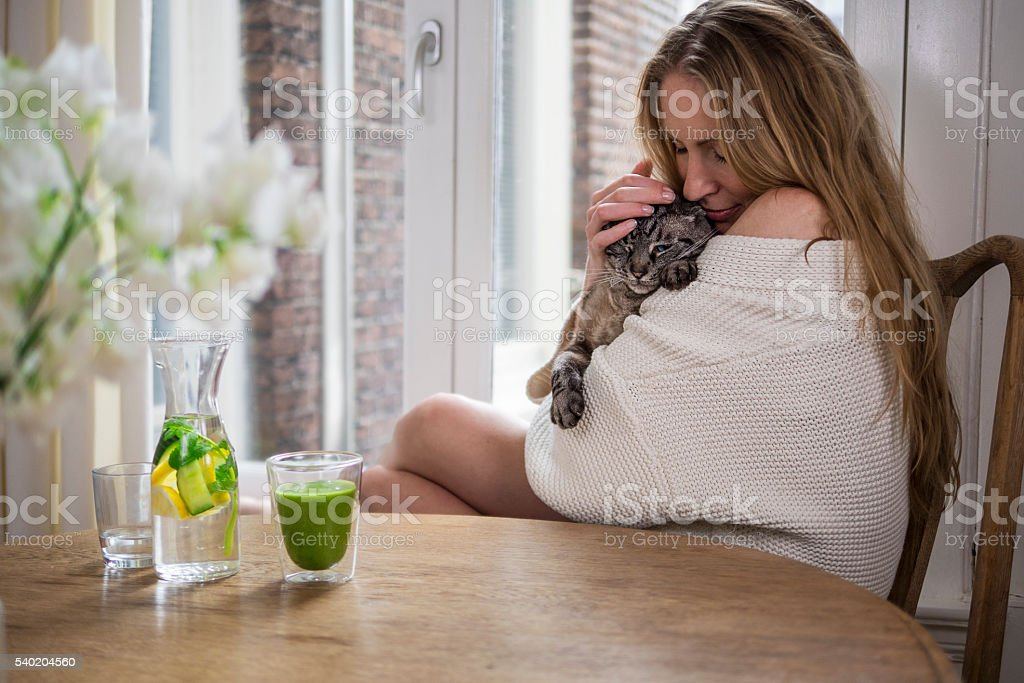 woman cuddling her cat in the morning stock photo