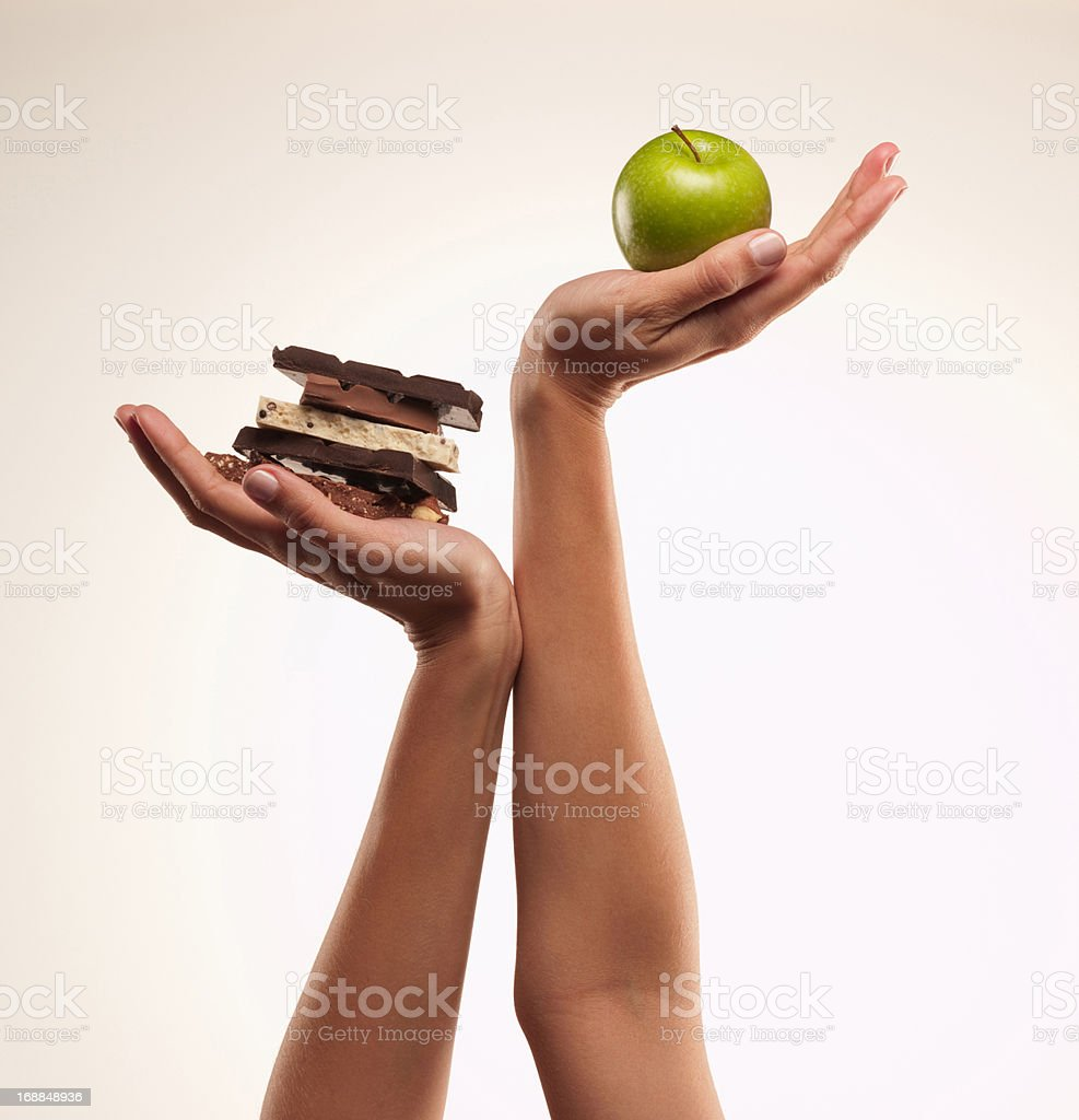 Woman cupping green apple above chocolate bars royalty-free stock photo