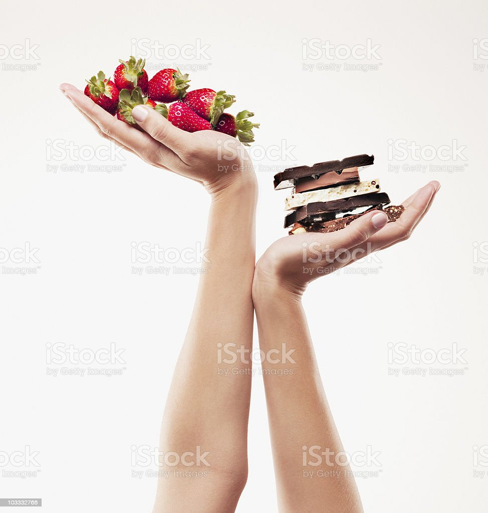 Woman cupping strawberries above chocolate bars stock photo