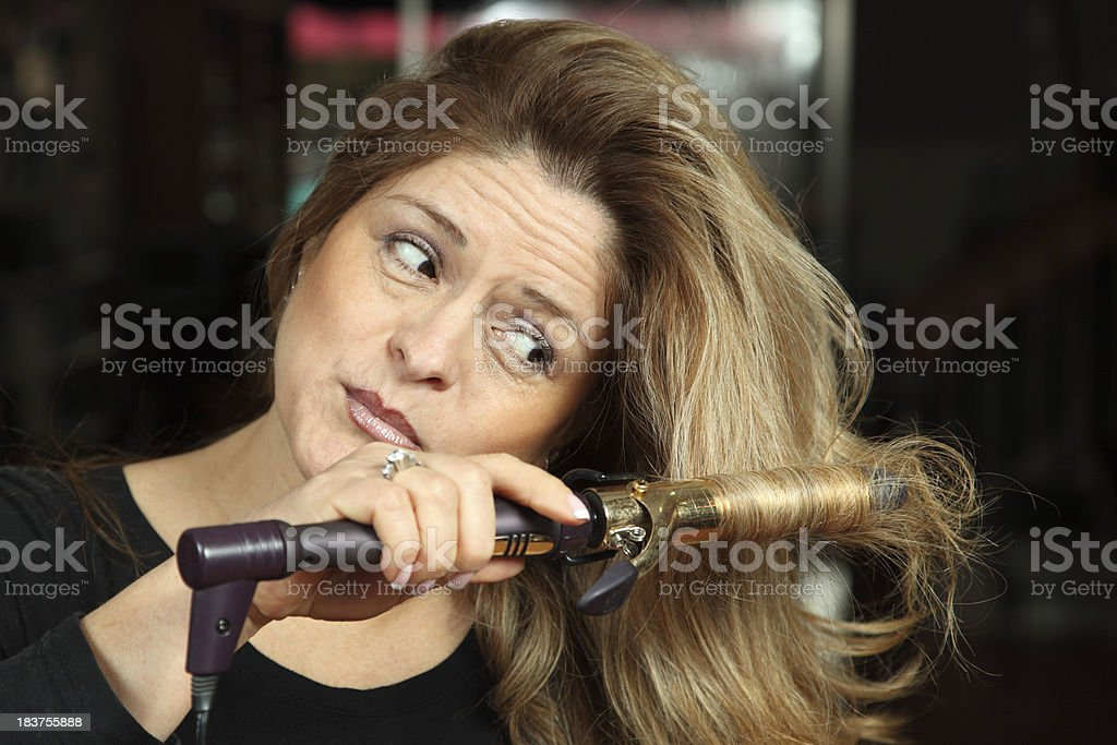 Woman curling hair with a curling iron and concerned look stock photo