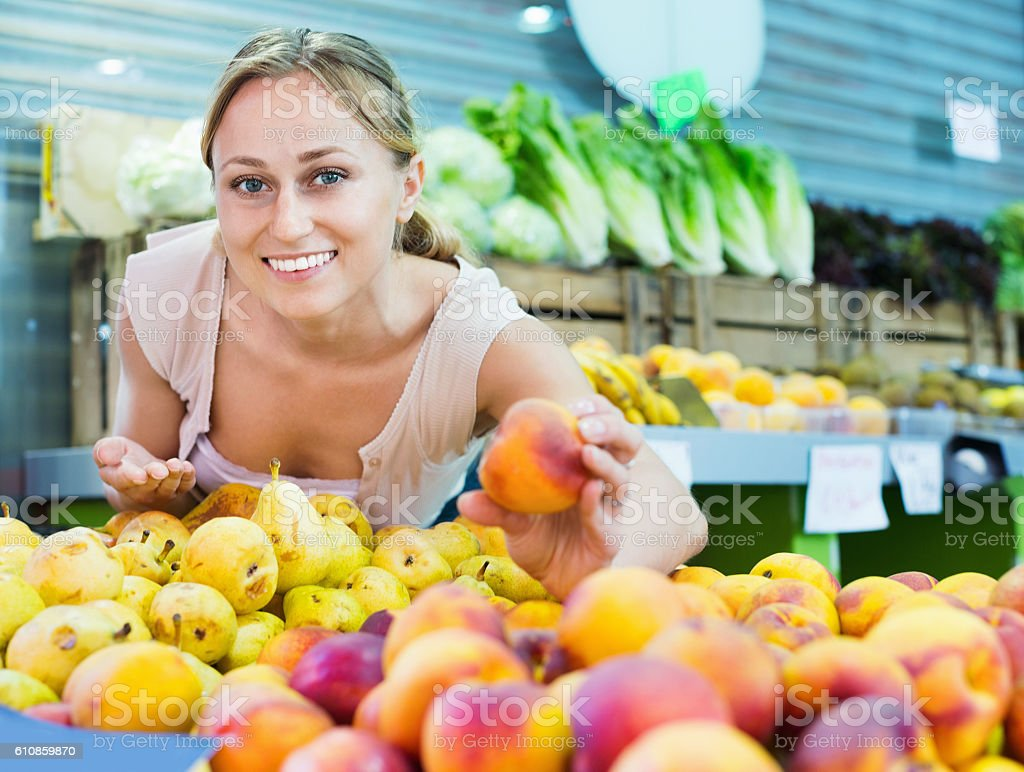 Woman customer choosing peaches on fruit market stock photo