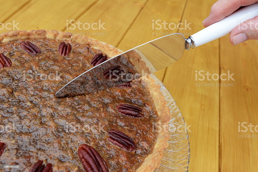 Woman cuts into a home-made pecan pie stock photo