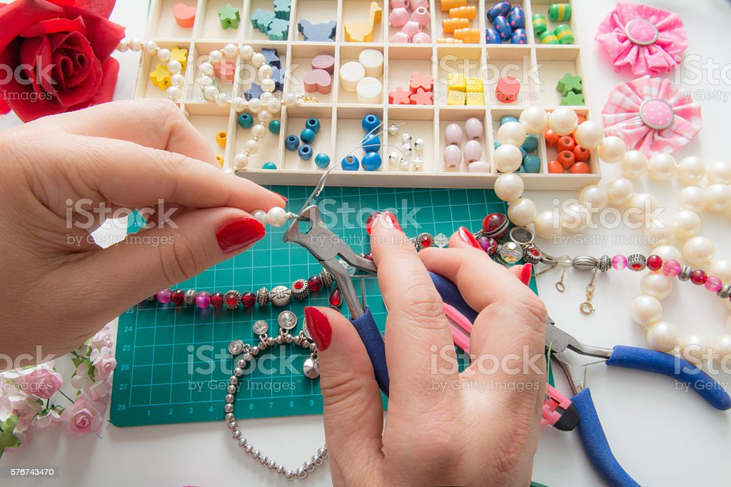 woman cuts with pliers strands from her pearl bracelet stock photo