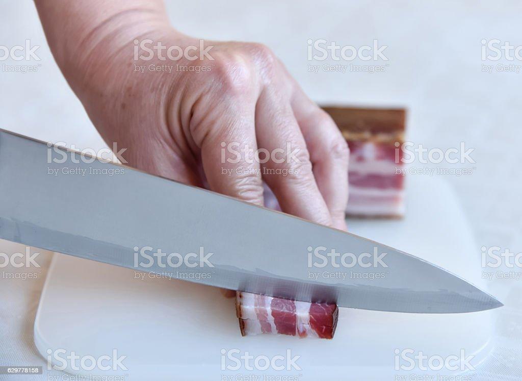 Woman cutting bacon stock photo