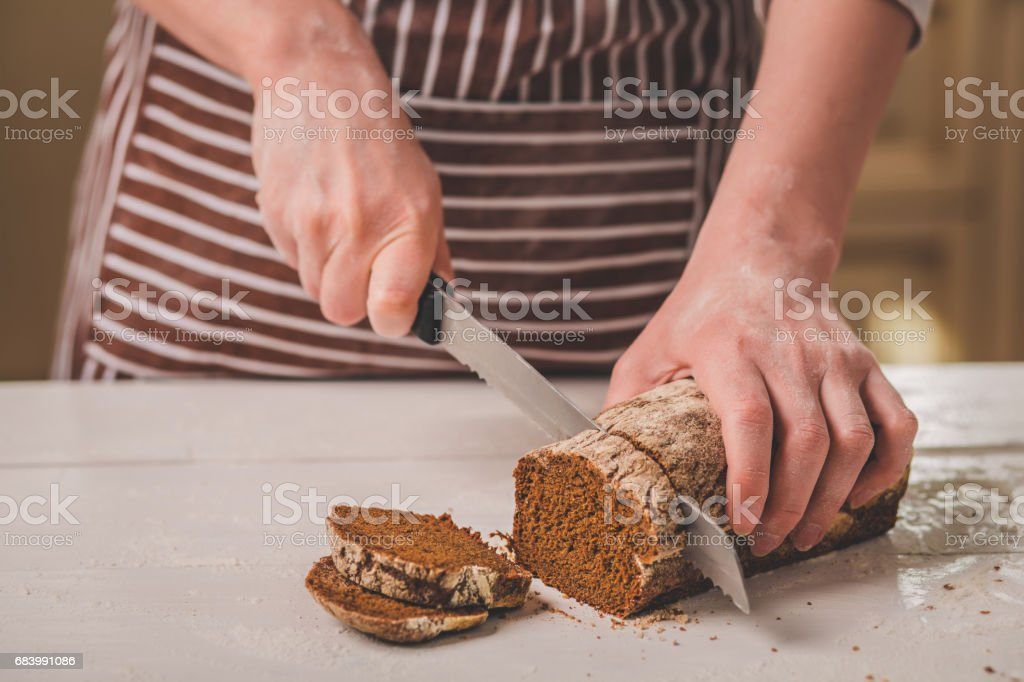 Woman cutting bread on wooden board. Bakehouse. Bread production stock photo