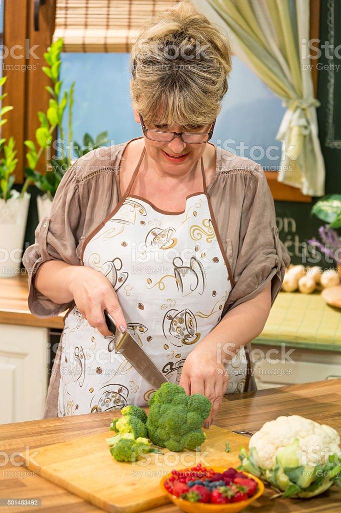 Woman cutting broccoli in kitchen. stock photo
