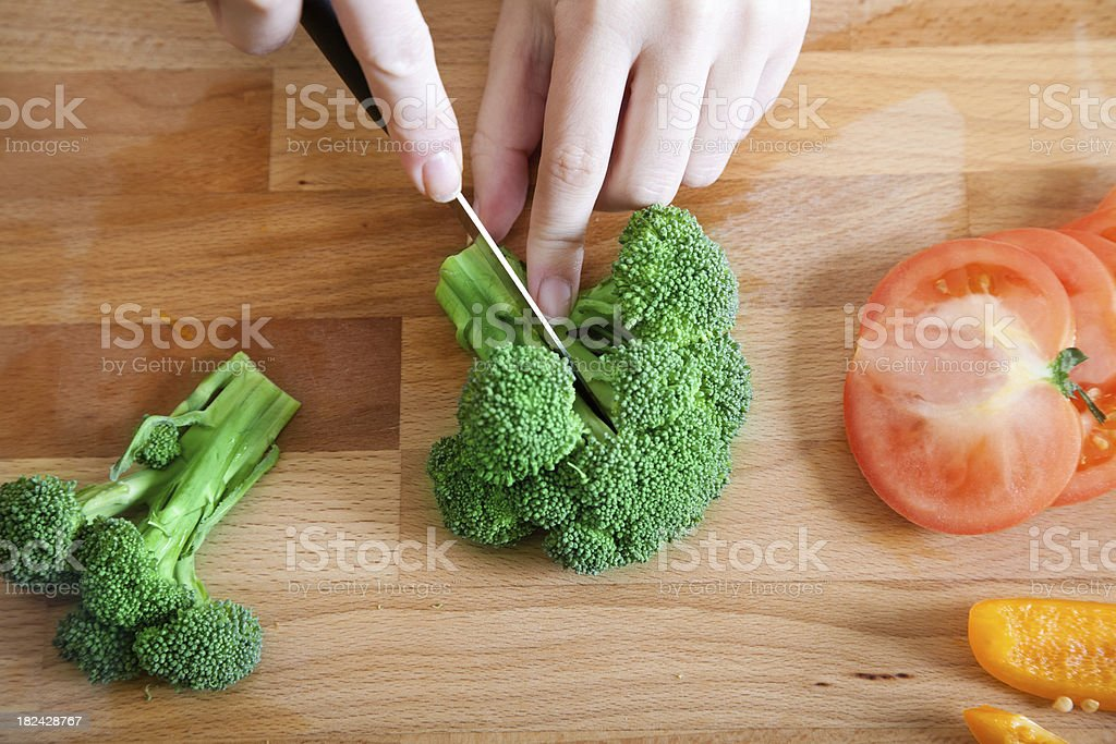 Woman Cutting Brocolli Into Slices with Other Vegetables royalty-free stock photo