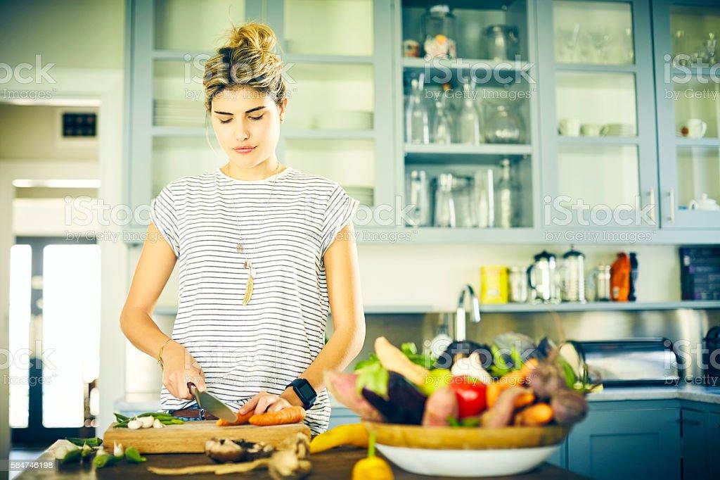 Woman cutting carrot at kitchen island stock photo