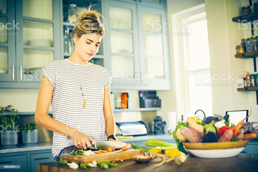 Woman cutting carrot with knife at kitchen island stock photo