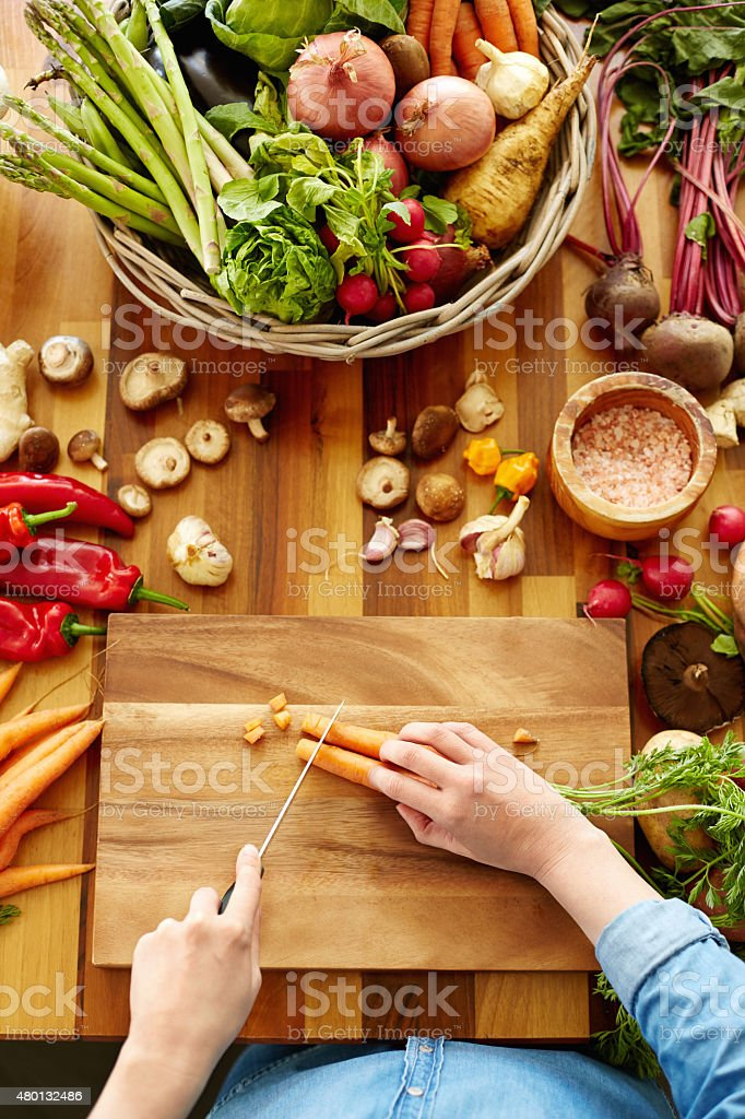 Woman cutting carrots on wooden board stock photo