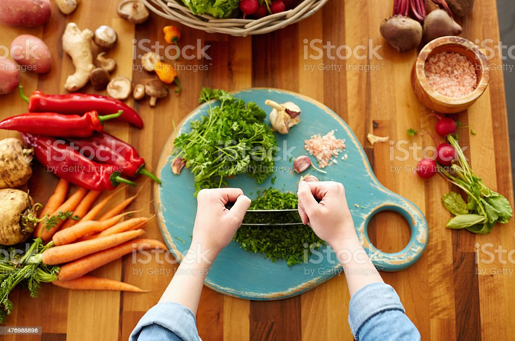 Woman cutting cilantro with mezzaluna knife stock photo