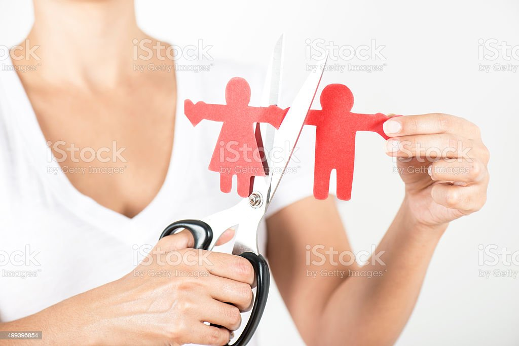 Woman cutting cut-out paper couple with scissors stock photo