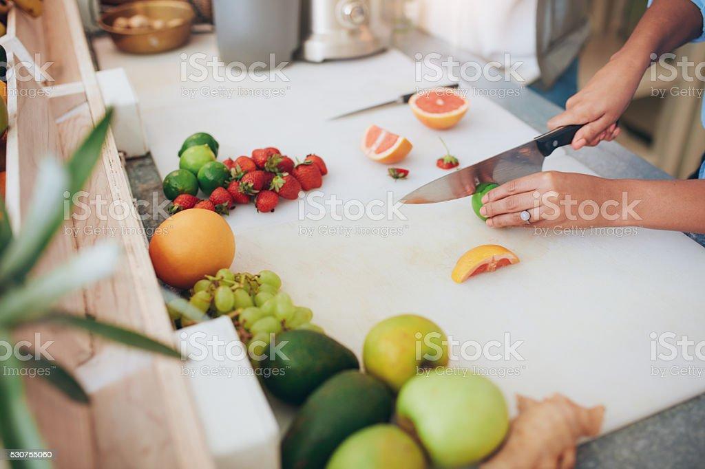 Woman cutting fruits at juice bar counter stock photo