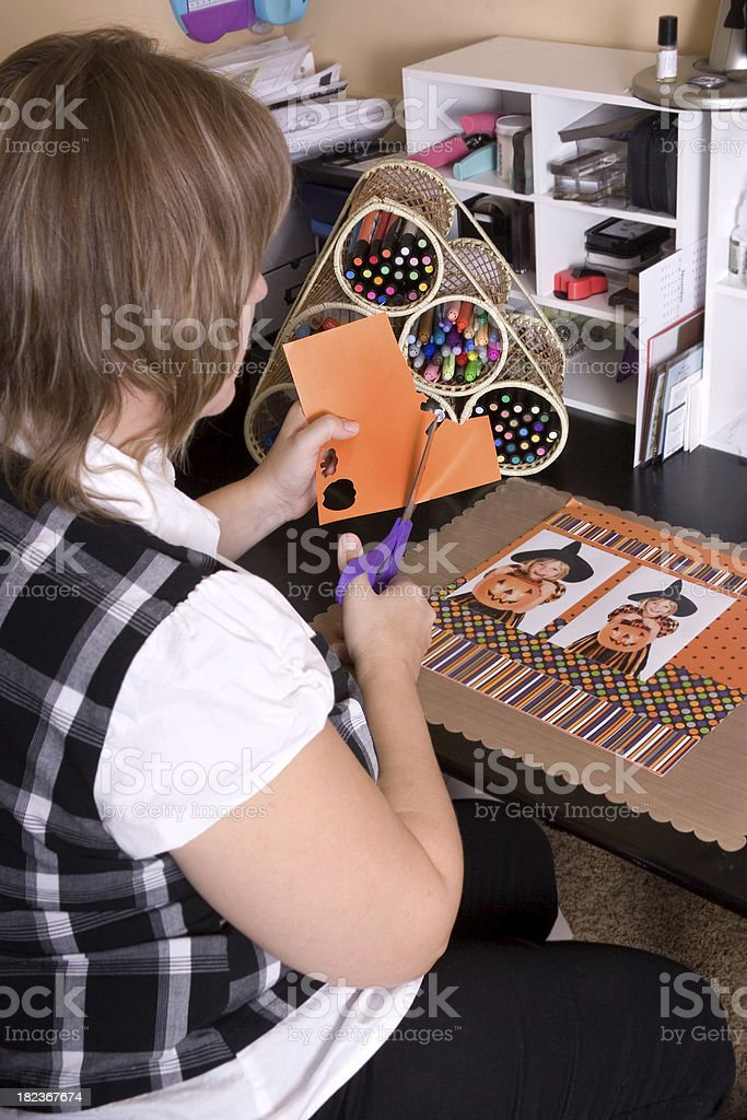Woman cutting paper for her scrapbook royalty-free stock photo