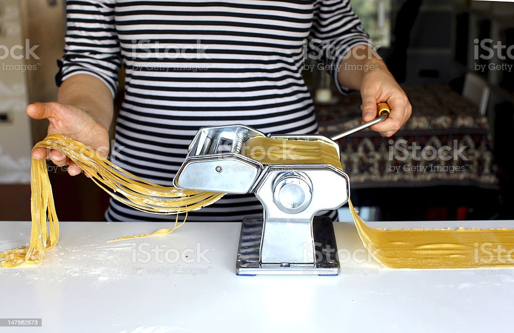 Woman cutting pasta dough on the machine stock photo