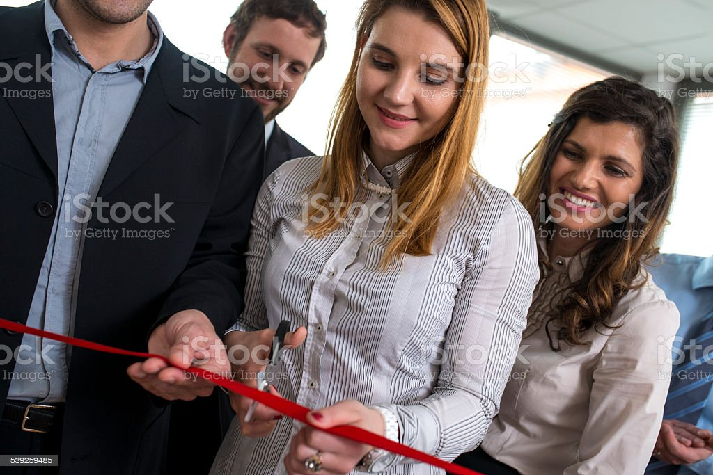 Woman cutting red ribbon with smiling onlookers beside. stock photo
