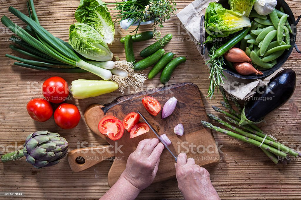 Woman cutting vegetable for lunch stock photo
