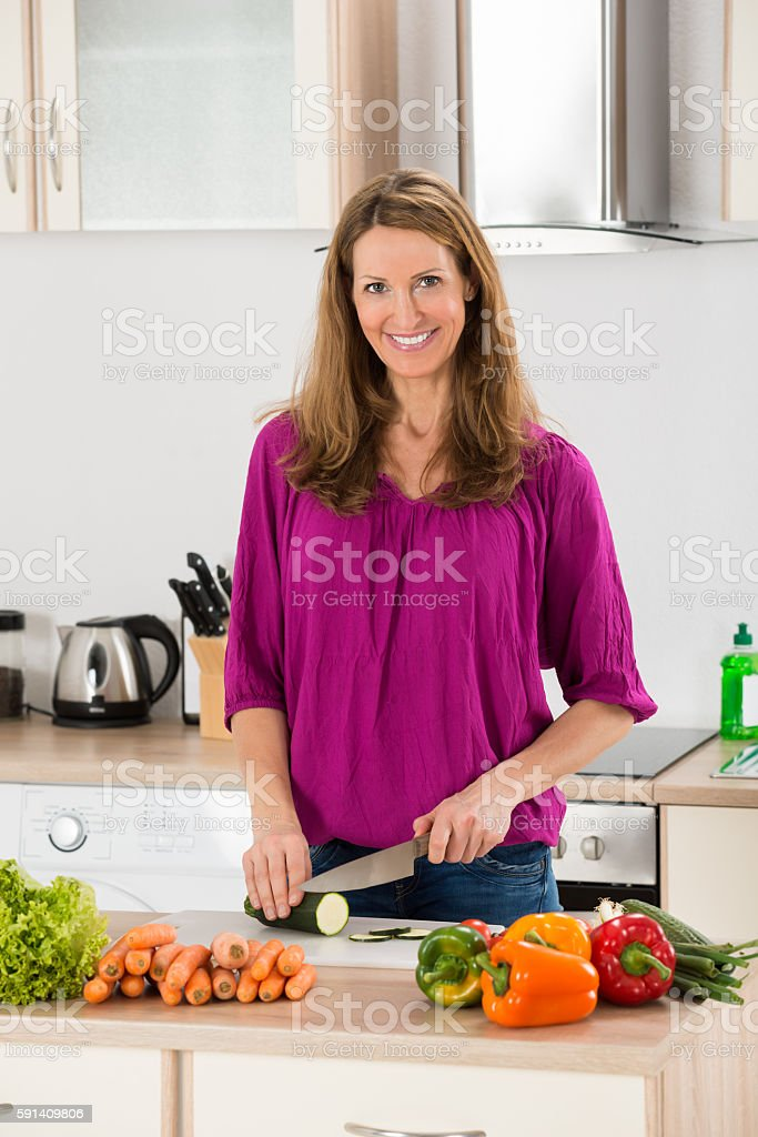 Woman Cutting Vegetable In Kitchen stock photo