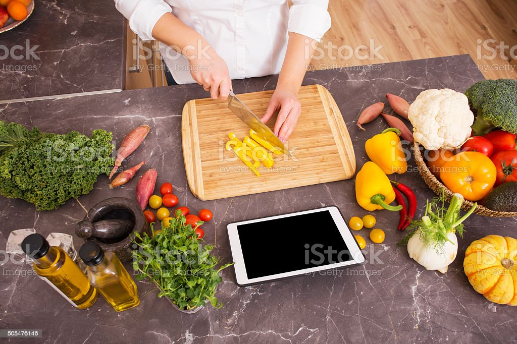 Woman cutting vegetable in pieces stock photo