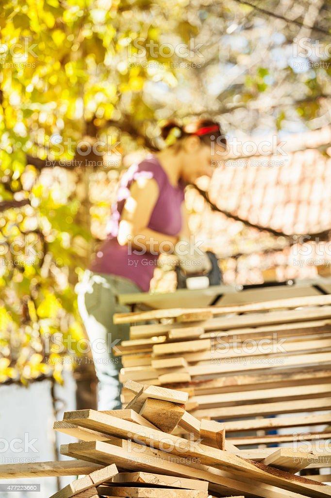 Woman cutting wood, selective focus stock photo