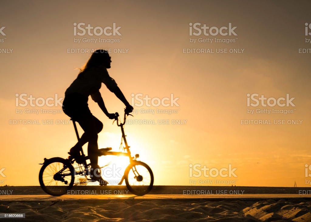 Woman cycling at Venice Beach royalty-free stock photo