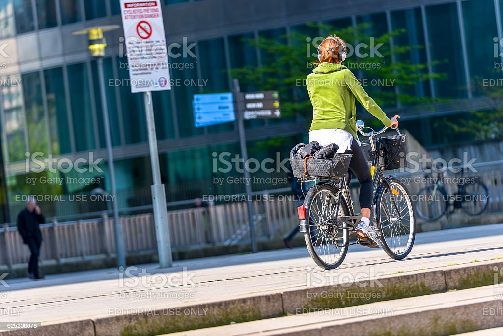 woman cycling by listening to music with headphones stock photo
