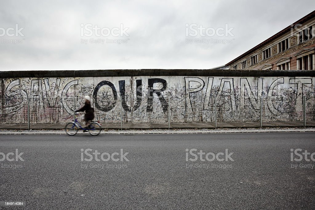Woman Cycling in Front of Berlin Wall, East Side, Germany stock photo