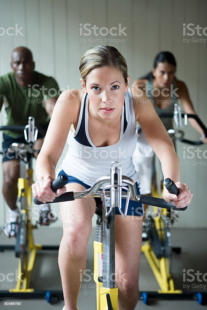 A woman cycling on an exercise bike stock photo