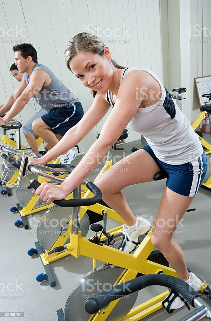A woman cycling on an exercise bike royalty-free stock photo