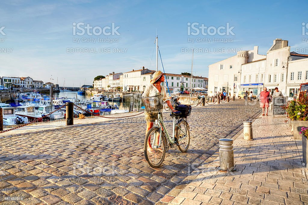 Woman cycling on harbour at St Martin-De-Re stock photo