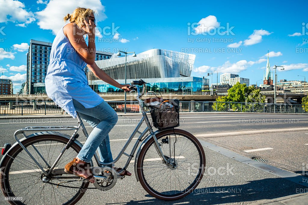 Woman cycling on Stockholm street, Sweden stock photo