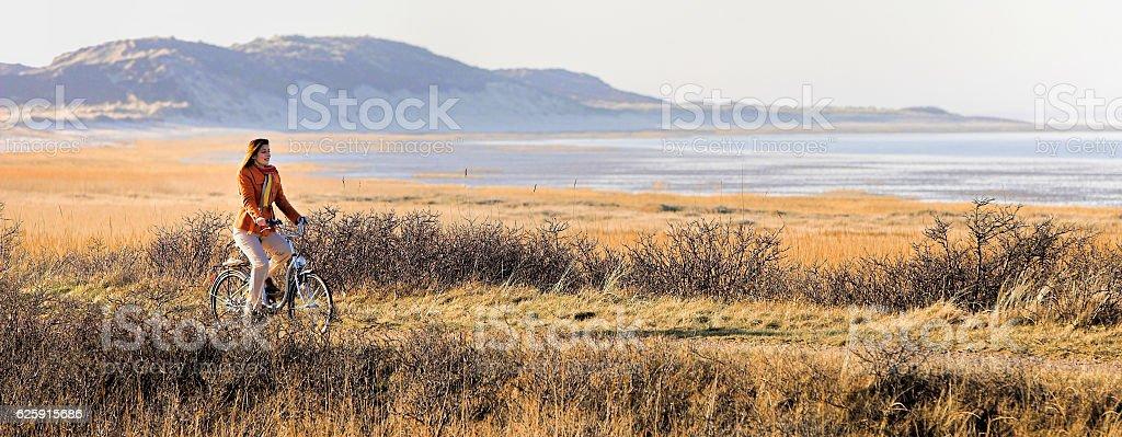 Woman cycling seaside on island Sylt stock photo