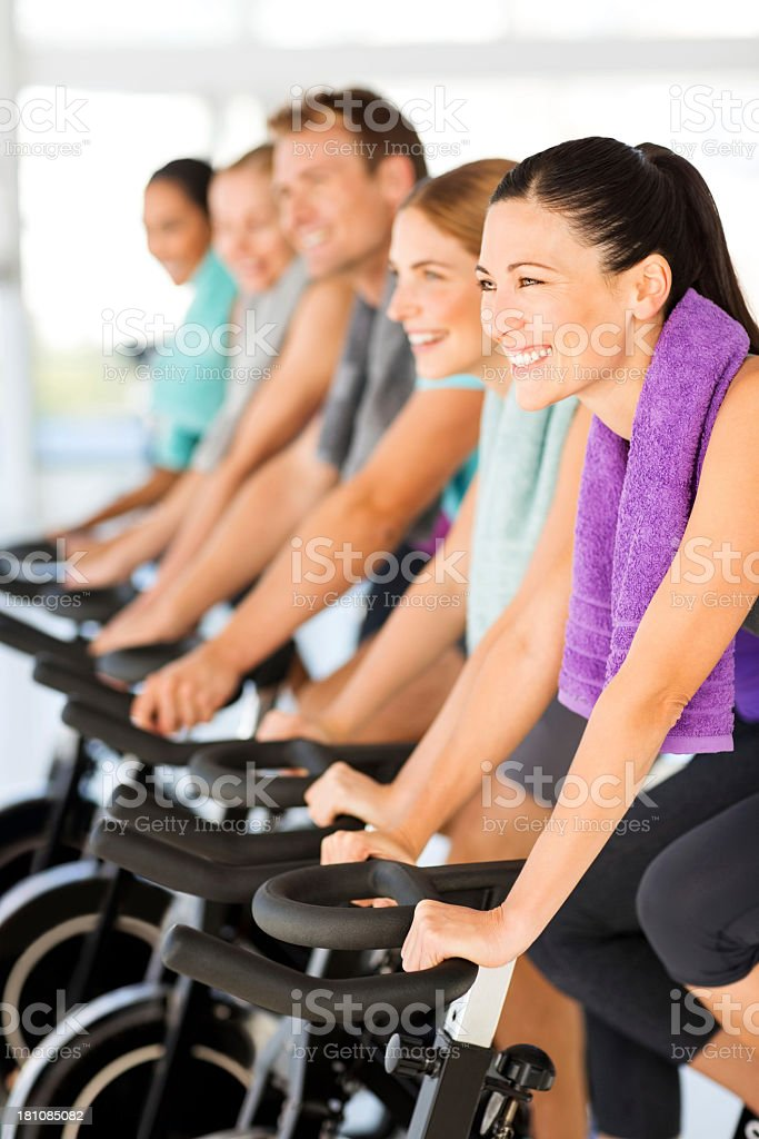 Woman Cycling With Friends On Exercise Bikes In Gym royalty-free stock photo