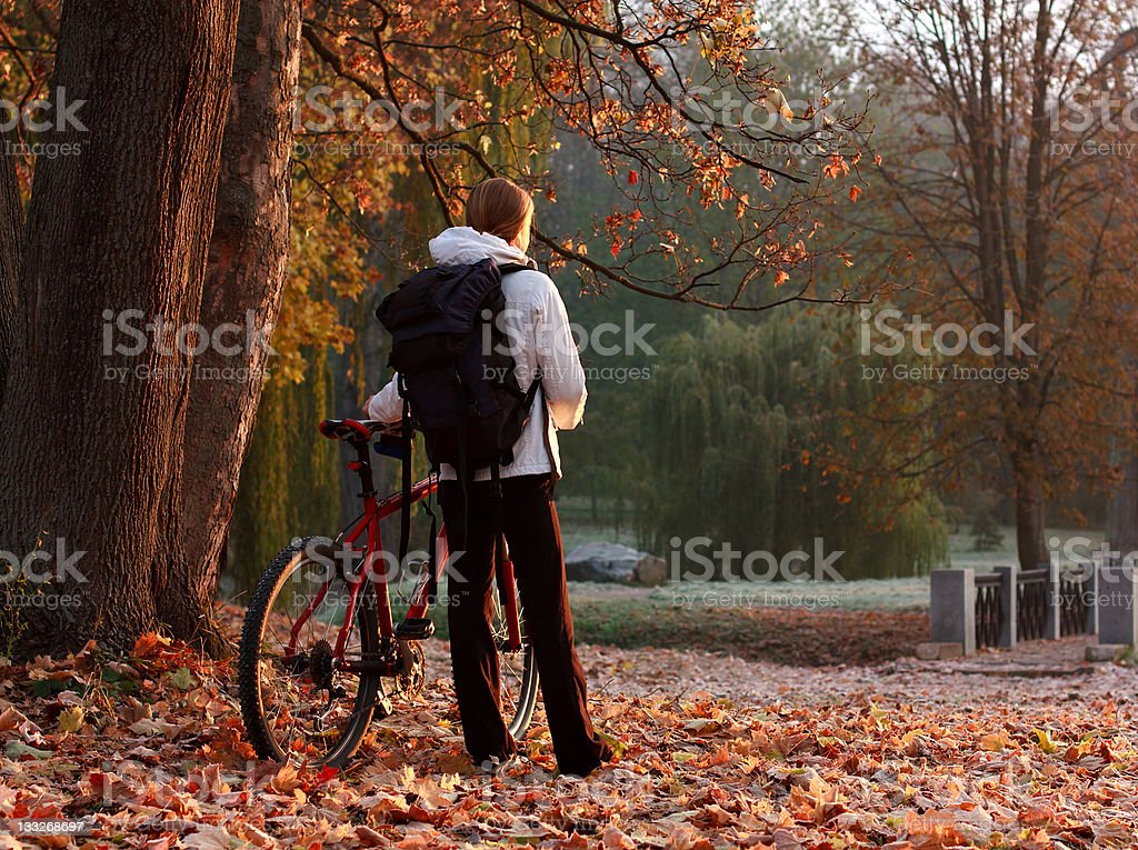 Woman cyclist with bike and backpack in autumn park royalty-free stock photo
